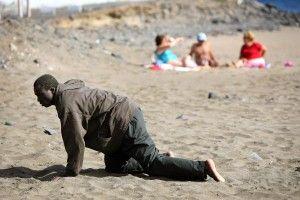 Un inmigrante a los posibles arrastra en la playa después de su llegada en un barco improvisado en la playa de Gran Tarajal, en la isla de España canaria de Fuerteventura en esta foto de archivo del 05 de mayo 2006. Juan Medina: