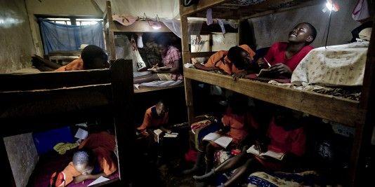Estudiantes leen sus libros gracias a la luz acumulada durante el día   de las placas solares en el dormitorio de la escuela de Kirugaluga