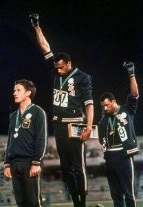 Smith y Calos en el podio con el puño alzado en el momento de escuchar el himno americano.
