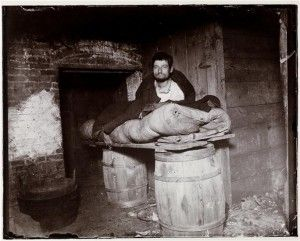 One of four pedlars who slept in cellar of 11 Ludlow Street rear. Un hombre duerme sobre dos barriles en un sótano.