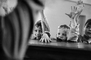 Zurich. 1955. Special school for deaf-mute children that teaches them to hear through their vibratory senses. Music education. Children raise their hands according to the teacher's instructions when they have heard with their fingertips the lively rythm played on the piano. © Rene Burri/Magnum Photos