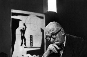 Le Corbusier ante los planos de una ciudad. Detrás suyo, una litografía del 'Modulor'
