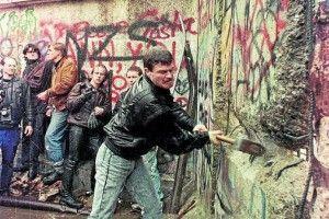 Un hombre con un martillo golpea el muro que dividió durante 28 años Berlín y Alemania