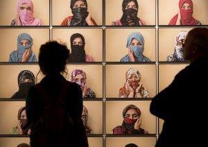 Visitantes en la exposición ante retratos de mujeres del correccional de menores.