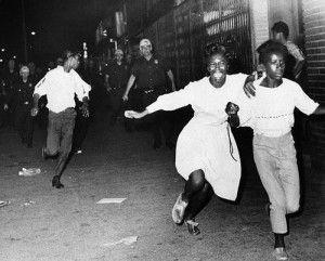 Manifestantes negros corren frente la policia en Watts, Los Angeles, en 1965