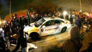 Disturbios en Ferguson. Los manifestantes atacan un coche de policia