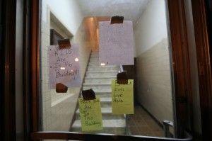 """Papeles pegados en el cristal de un edificio en el que se puede leer: """""""