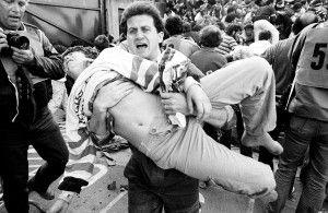 Un aficionado al fútbol heridos se lleva a un lugar seguro por un amigo después de una pared se derrumbó durante la violencia entre los aficionados antes de la final de la Copa de Europa entre la Juventus y el Liverpool en este 29 de mayo 1985 foto de archivo en el estadio Heysel de Bruselas. 39 personas murieron y otros 600 resultaron heridos. REUTERS / Nick Didlick