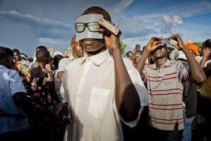 Un espectador observa el eclipse a través de una lámina de plástico rígido y opaco que puso entre sus ojos y las gafas
