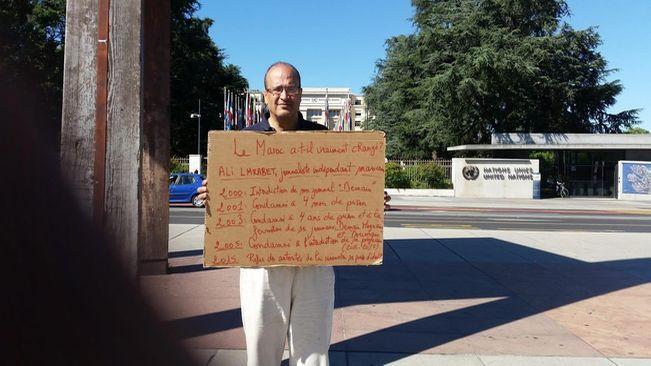 Lmrabet muestra un cartel denunciando las condenas y persecuciones sufridas en Marruecos