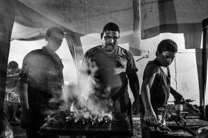 VISTA HERMOSA PRISON, CIUDAD BOLIVAR, VENEZUELA - MARCH 2013: With his two sons, a prisoner grills meat to sell to other inmates and their visitors. Since Wilmito and his gang took control of Vista Hermosa by force, the inmates  have the freedom to run their our businesses in the prison. (Photo by Sebastián Liste/ Reportage by Getty Images)